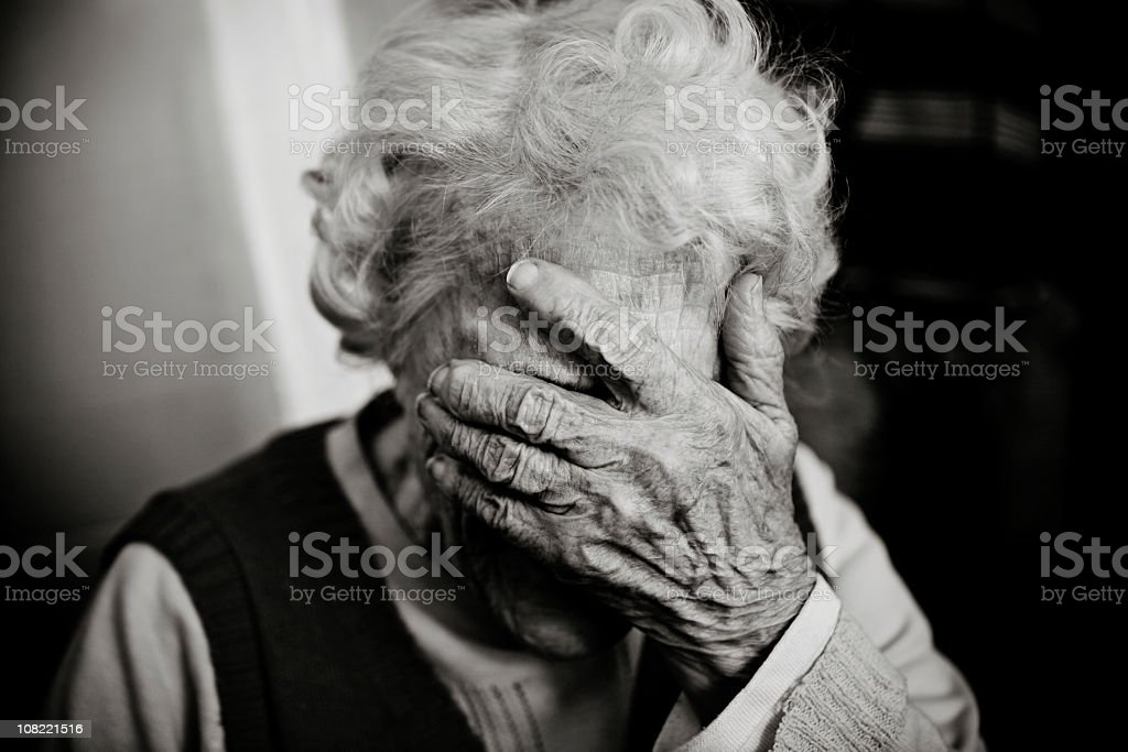 Senior Woman Holding Head in Hand, Black and White stock photo