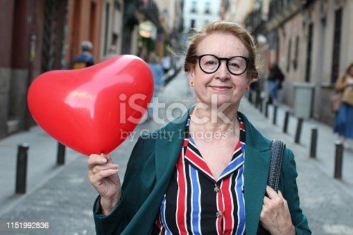 istock Senior woman holding heart balloon outdoors 1151992836