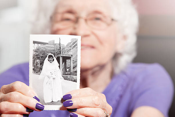 Senior Woman Holding Her Wedding Photo stock photo