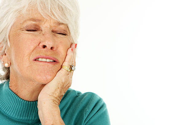 Senior woman holding jaw indicating toothache  stock photo