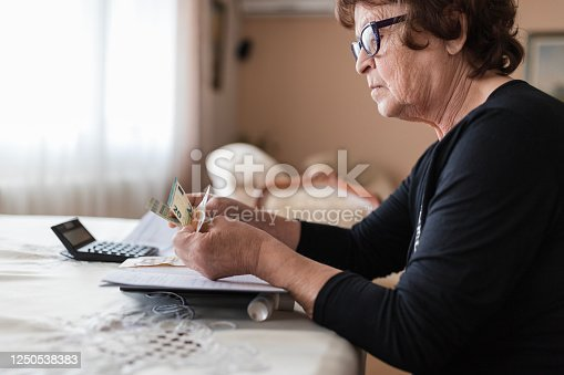 istock Senior woman holding money in her hands at home 1250538383
