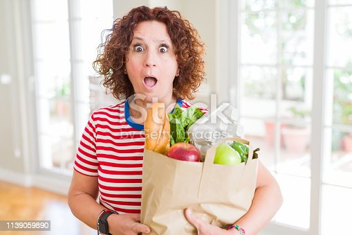 Senior woman holding paper bag full of fresh groceries from the supermarket scared in shock with a surprise face, afraid and excited with fear expression
