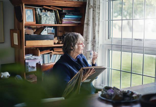 senior vrouw met fotoalbum sip's thee, kijkend naar venster - senior fotoboek stockfoto's en -beelden
