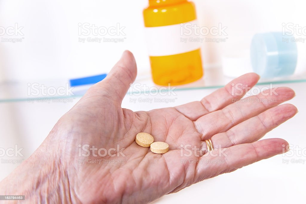 Senior woman holding pills in front of medicine cabinet stock photo