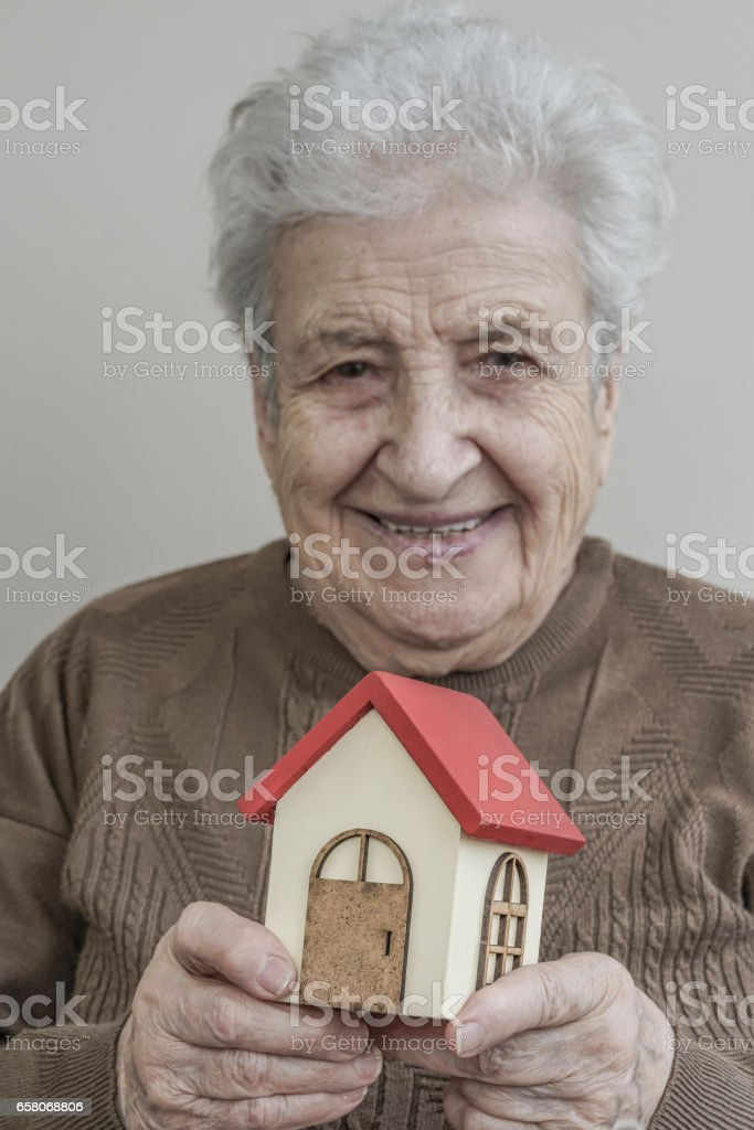 Senior woman holding small wooden house royalty-free stock photo