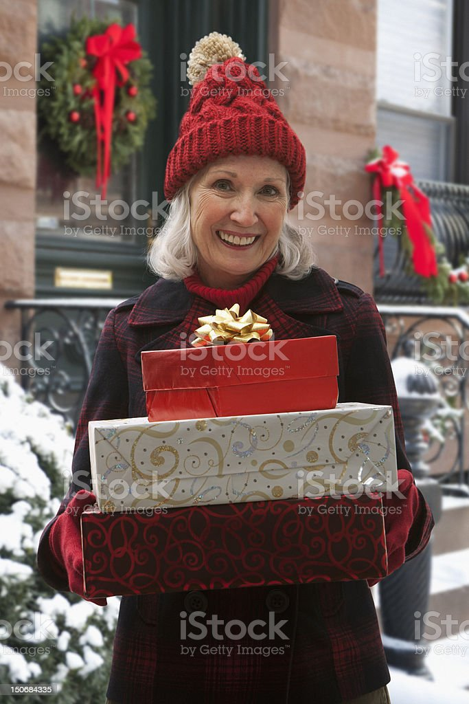 Senior woman holding stack of gifts royalty-free stock photo