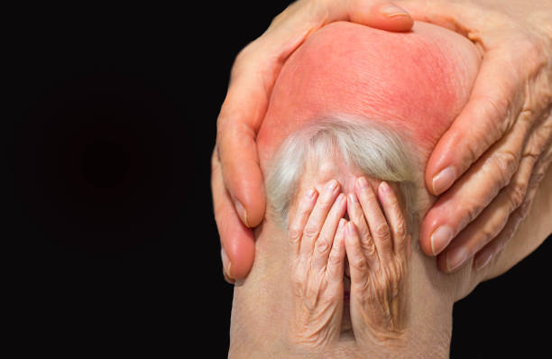 Senior woman holding the knee with pain stock photo