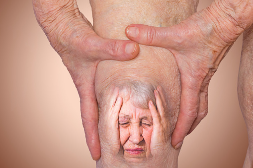 Senior woman holding the knee with pain. Collage. Concept of abstract pain and despair. The elderly pensioner and her problems. Old age and illnesses. 86-year-old Caucasian model. healthcare concepts