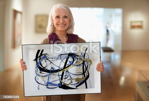 istock Senior woman holding up designs 150684349