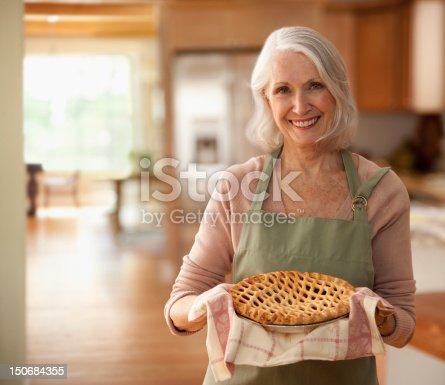 istock Senior woman holding up pie 150684355