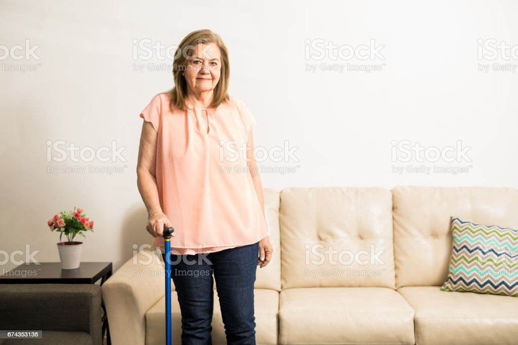 Senior woman holding walking stick for support stock photo