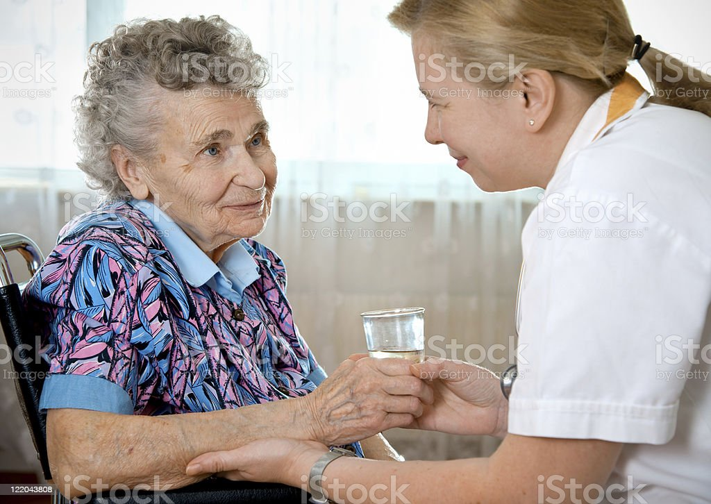 Senior woman holding water glass with caregiver royalty-free stock photo