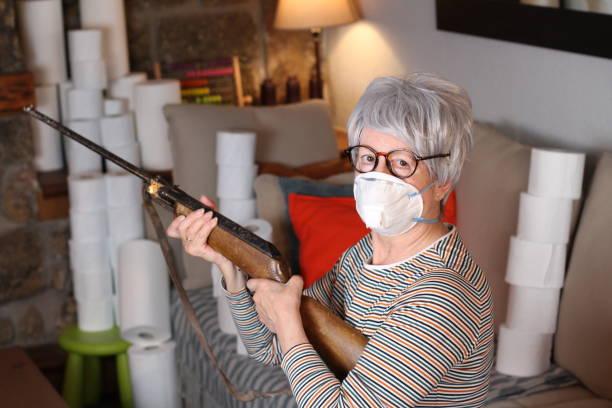 Mulher idosa segurando arma durante quarentena - foto de acervo