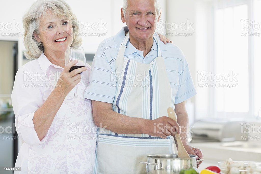 Senior woman holding wine glass by man while preparing food royalty-free stock photo