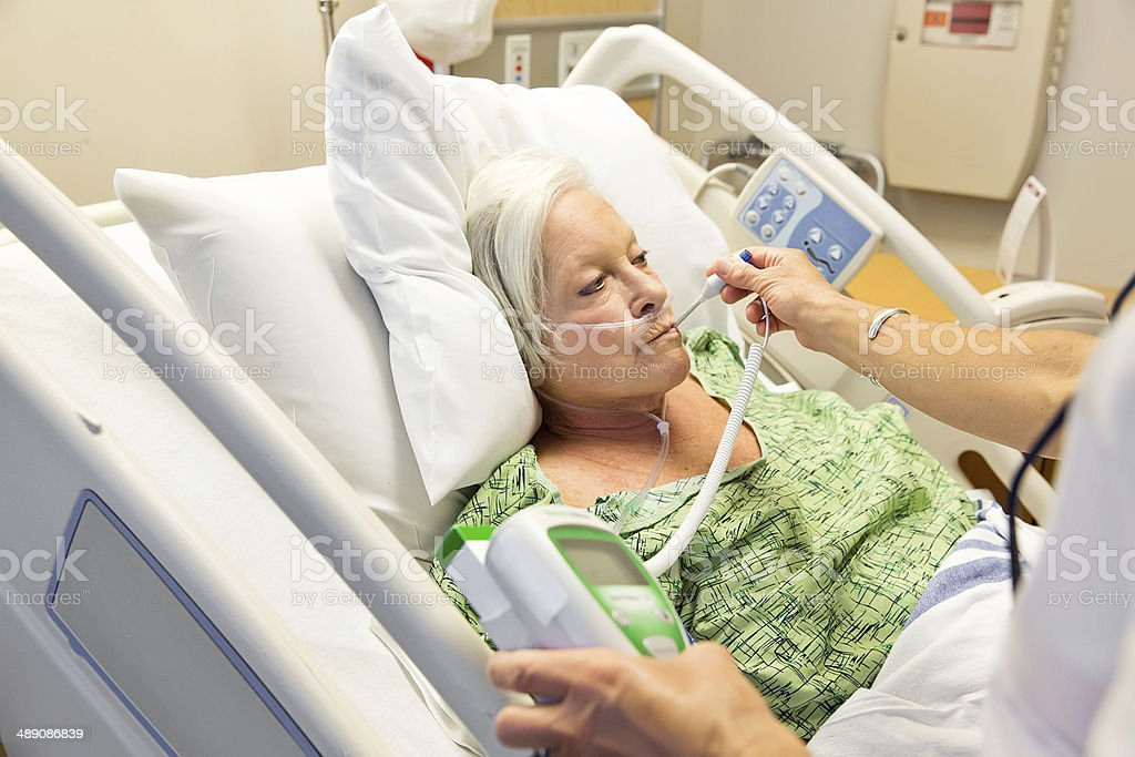Senior woman hospital patient having her temperature taken stock photo
