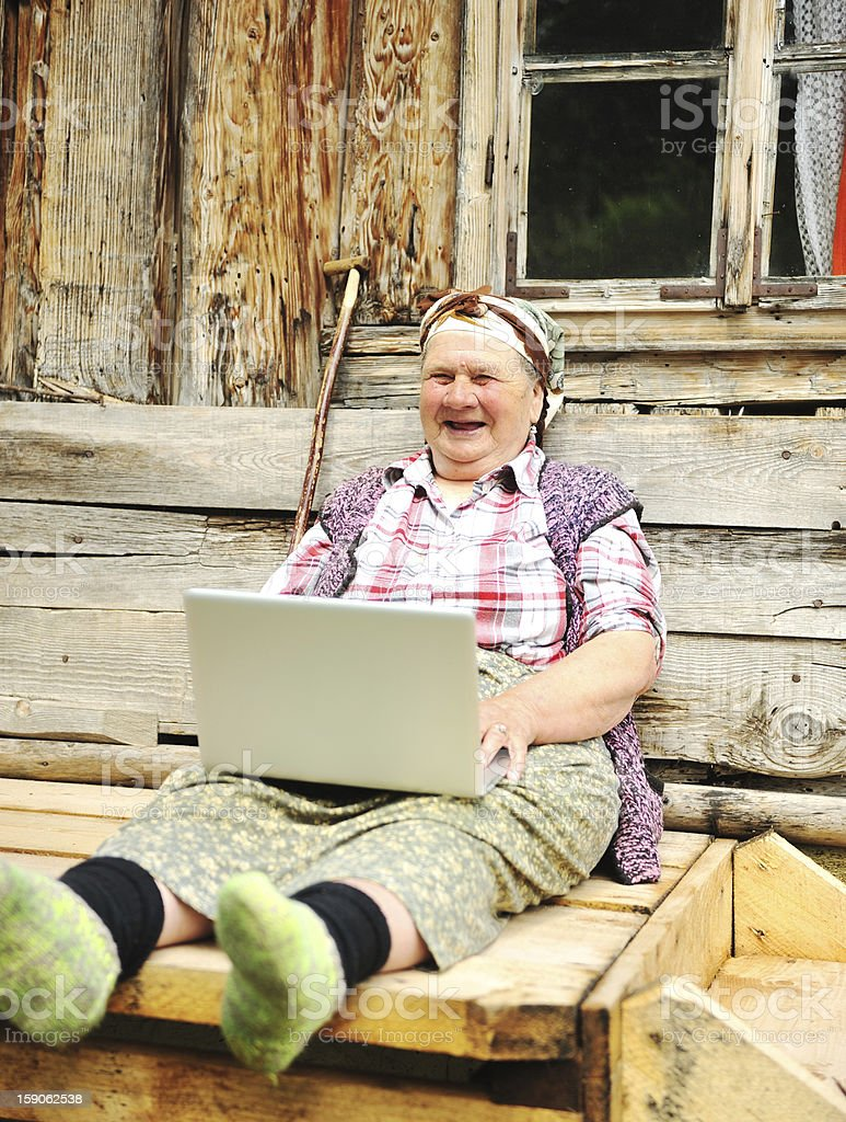 Senior woman in aged country environment working on laptop stock photo