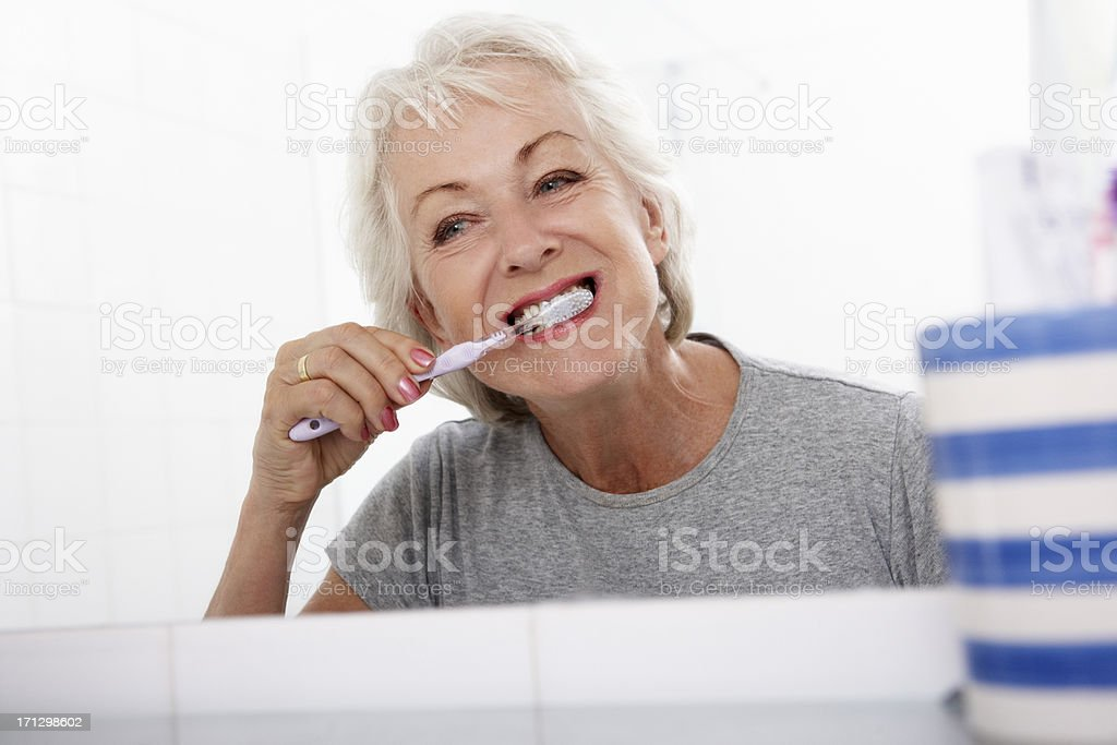 Senior Woman In Bathroom Brushing Teeth stock photo