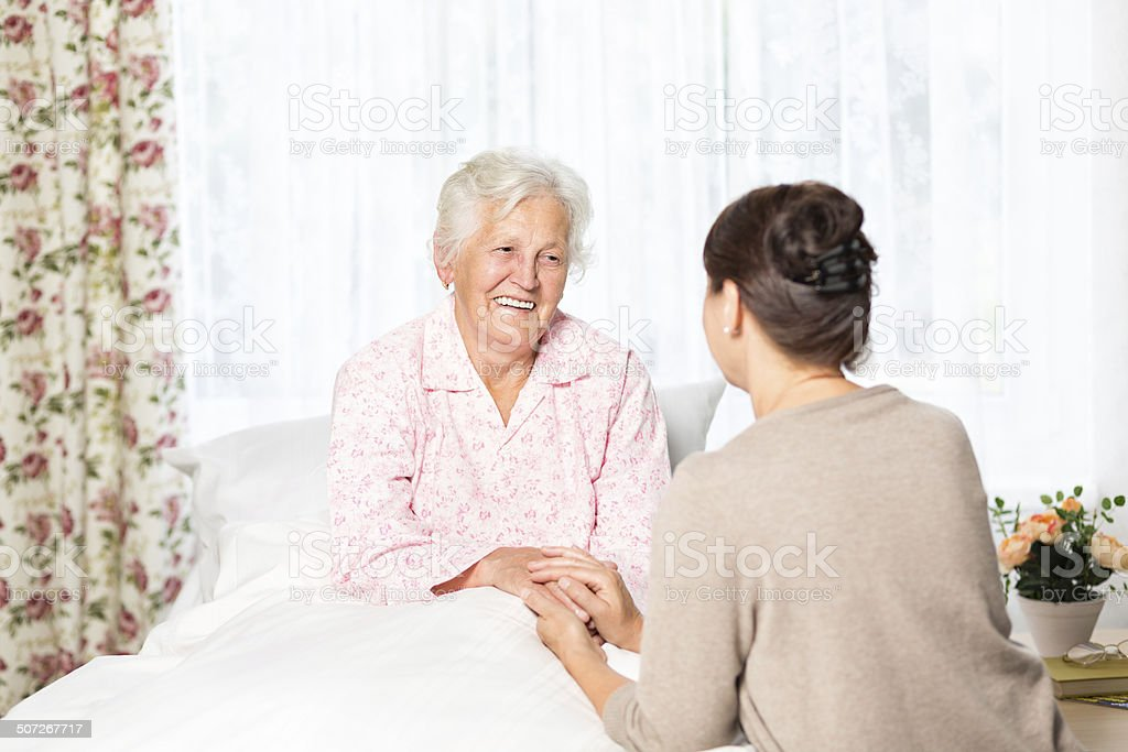 Senior woman with caregiver, from the series \'senior woman in bed at...