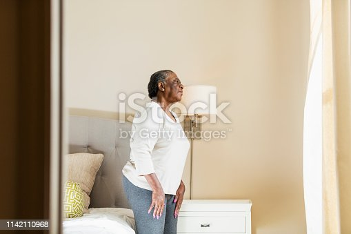 949450544istockphoto Senior woman in bedroom looking out window 1142110968