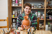 Senior woman in casual clothes and aprons at pottery workshop painting pottery. hobby on pension