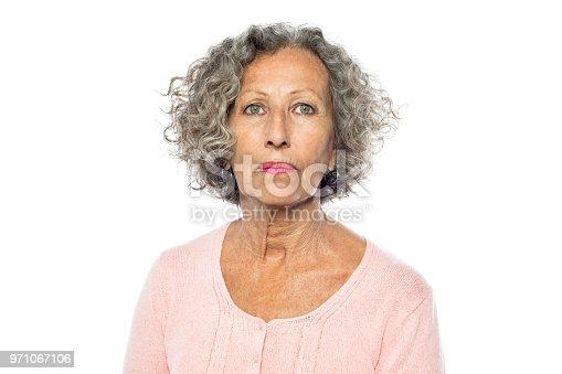 Portrait of senior woman in casuals looking serious against white background. Caucasian woman with short grey hair.