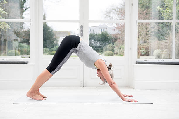 Senior woman in downward dog position stock photo