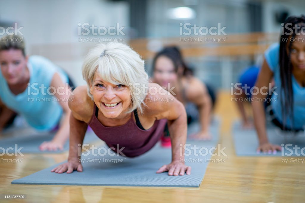 Senior vrouw in fitness klasse in een plank pose lachende stockfoto - Royalty-free 35-39 jaar Stockfoto