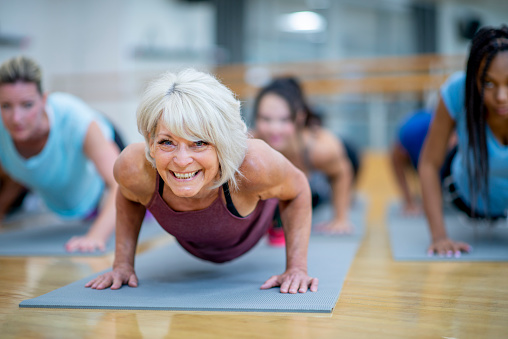 An older Caucasian woman is seen holding a plank pose while participating in a  co-ed, multi-ethnic, fitness class.  She is smiling and appearing to enjoy the class.