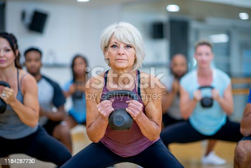 An older Caucasian woman is seen doing a squat with a kettlebell, while participating in a co-ed, multi-ethnic, fitness class.  She is expressionless and focusing on her form.