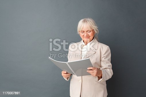 istock Senior woman in fromal suit and glasses studio standing isolated on gray reading journal smiling joyful 1170007891
