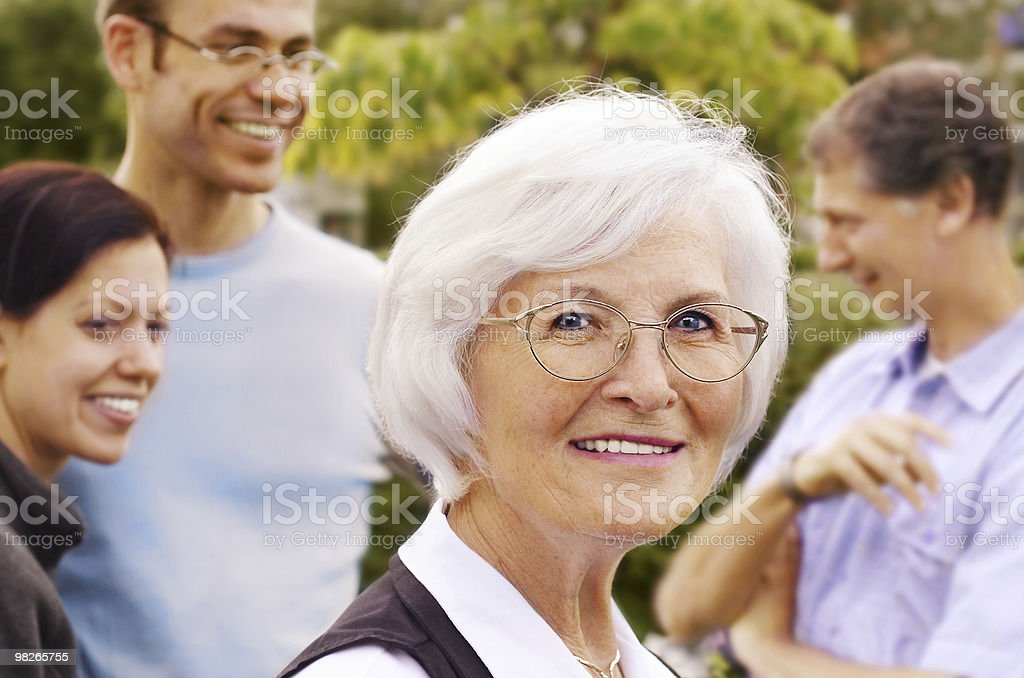 Senior woman in front of young people group royalty-free stock photo