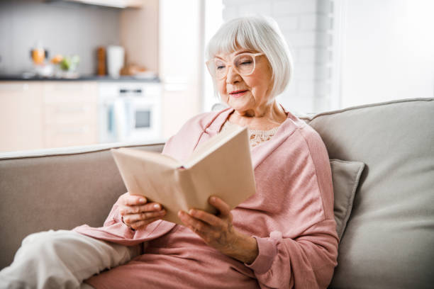 Senior woman in glasses reading book at home stock photo
