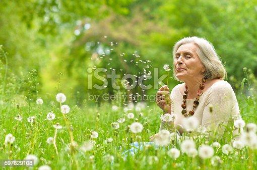 istock Senior woman in green park 597629108