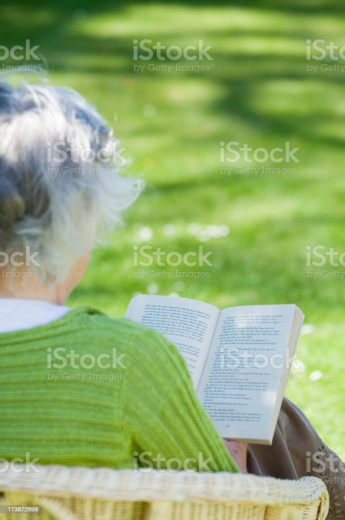 Senior woman in green shirt reading a book outdoors royalty-free stock photo