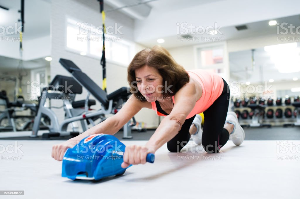 Senior woman in gym exercising abs with wheel roller stock photo