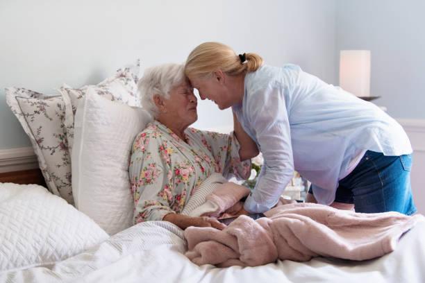 eine ältere frau in ihrem bett umarmte ihre tochter mit emotion - hospiz stock-fotos und bilder