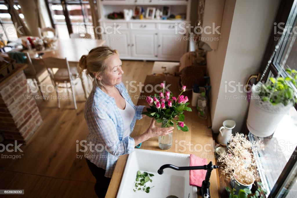 Senior Woman In Her Kitchen Arranging Roses In Vase Stock Photo