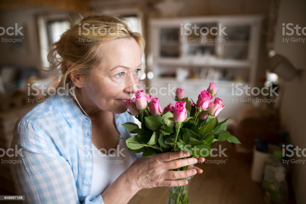 Senior woman in her kitchen smelling bouquet of pink roses стоковое фото