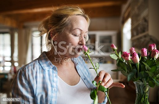 Beautiful senior woman at home in her kitchen smelling a fragrance of pink rose