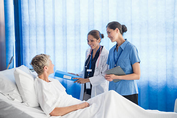 senior woman in hospital bed with two female medcial staff - australian nurses stock photos and pictures