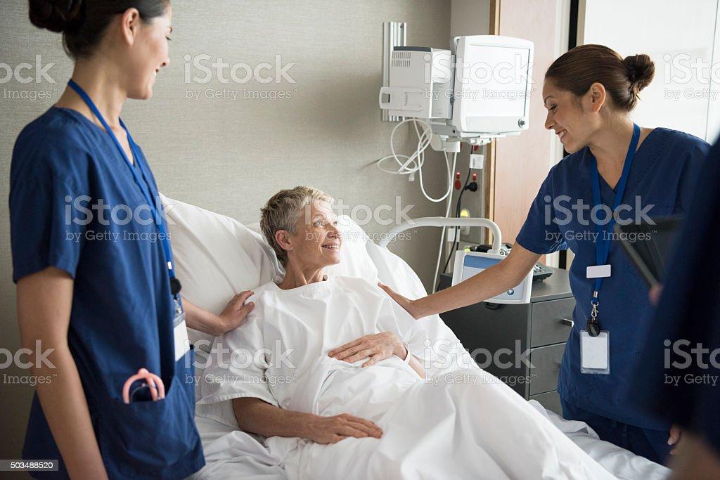 Senior woman in hospital bed with two female nurses, smiling stock photo