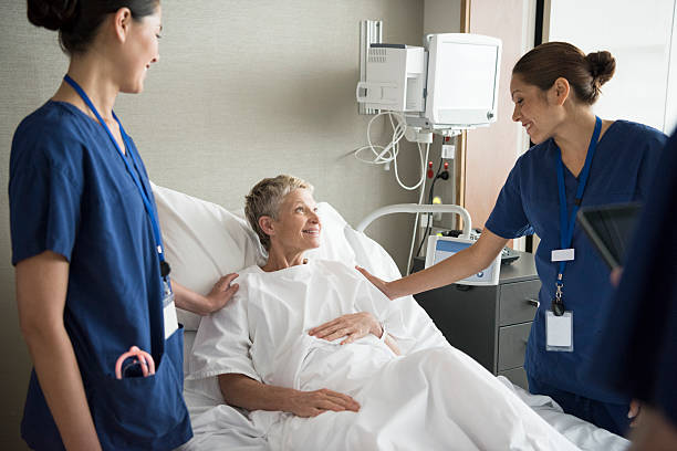 senior woman in hospital bed with two female nurses, smiling - australian nurses stock photos and pictures