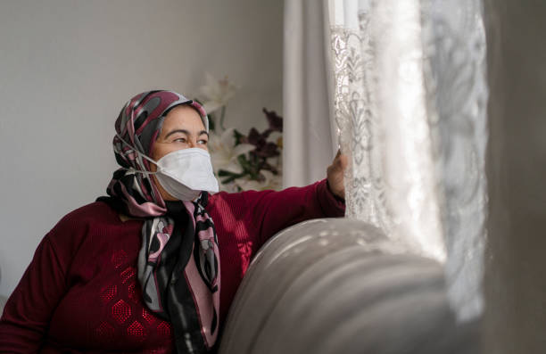 Senior woman in medical mask staying at home under quarantine stock photo