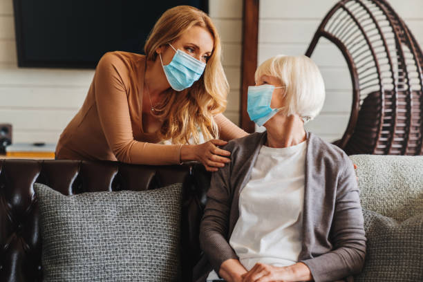senior woman in medical mask with social worker visiting her at home - visita foto e immagini stock