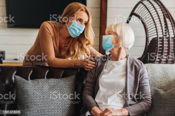 Hogere Vrouw In Medisch Masker Met Maatschappelijk Werker Die Haar Thuis Bezoekt Stockfoto en meer beelden van Ademhalingsstelsel