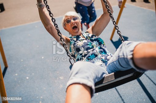 Senior woman on a child's swing in a public park. The sun is shining and she is laughing as she swings forward.