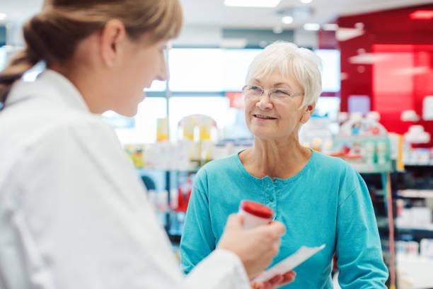 Seniorin in der Apotheke im Gespräch mit der Apotheke oder Apothekerin – Foto