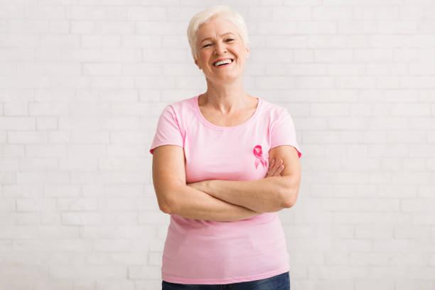 mulher sênior no t-shirt cor-de-rosa do cancro da mama que está sobre a parede branca - breast cancer - fotografias e filmes do acervo