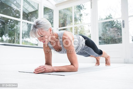 istock Senior woman in plank position in conservatory 513480944