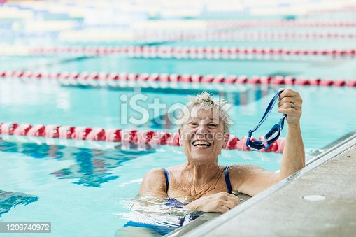 A senior woman in her 60s exercising in a swimming pool. She is hanging onto the side of the pool, taking a break after swimming laps, looking at the camera.